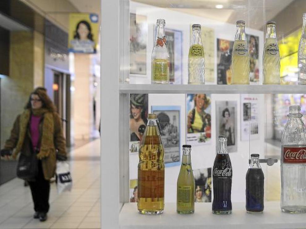 Imagen de una de las vitrinas colocadas en el Centro Comercial Augusta de Zaragoza, con envases de bebidas de distintas décadas.