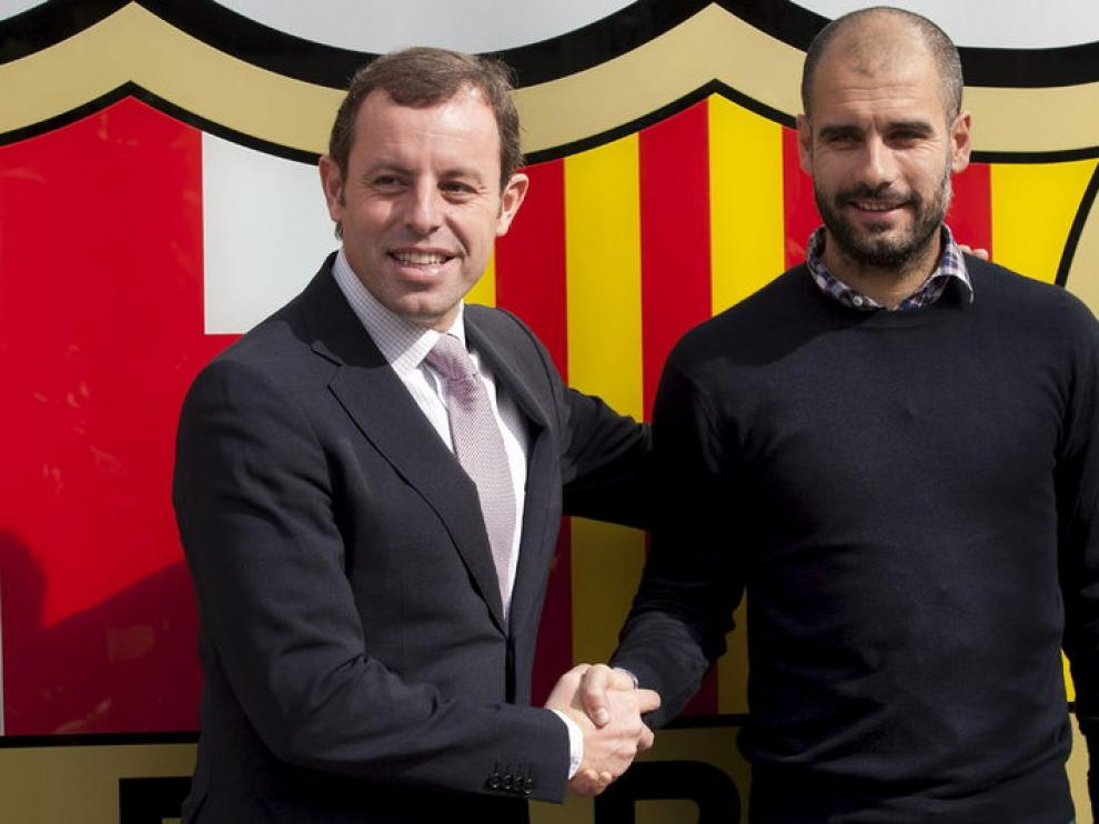 Guardiola y Rosell se estrechan la mano tras la firma del nuevo contrato del entrenador del Barça