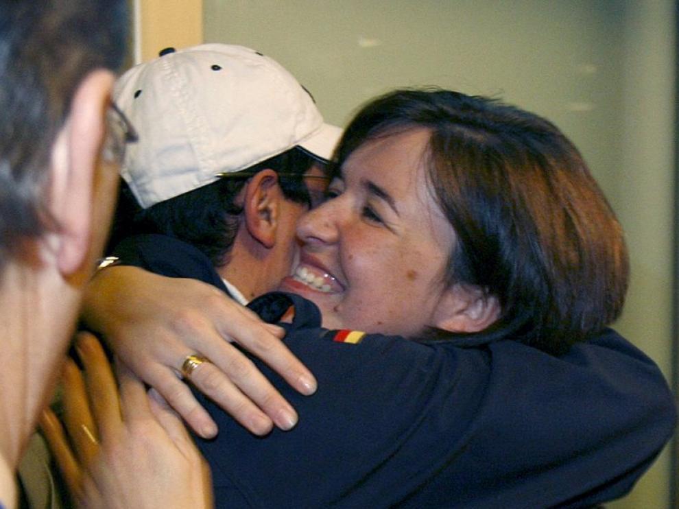 Una mujer abraza hoy en Barajas a un empleado de Repsol, recién llegado de Libia