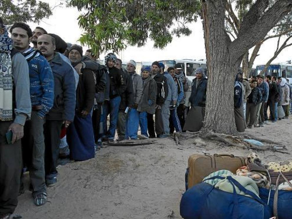 Egipcios hacen cola ante un hospital militar tunecino en el paso de Ras Jedir tras huir de Libia, ayer.