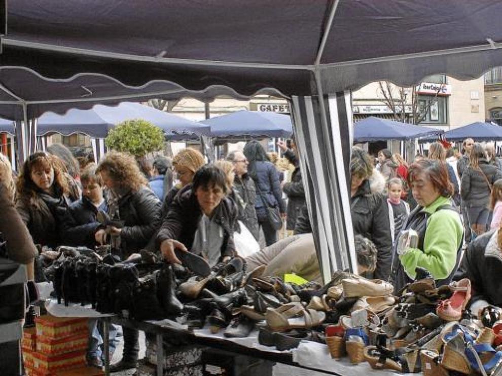 Un grupo de mujeres mira las ofertas de un puesto de zapatos, ayer en Caspe.