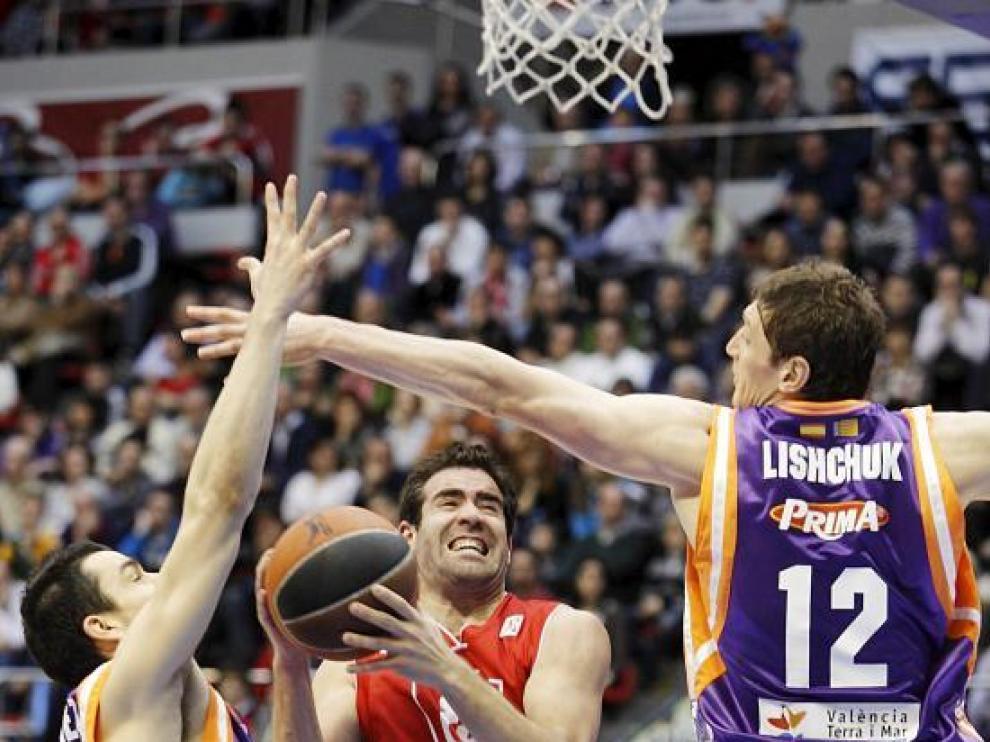 Carlos Cabezas salta hacia la canasta defendido por Rafa Martínez y Lishchuk.