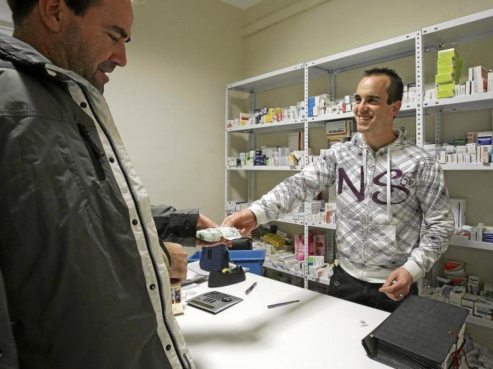 El farmacéutico de Loporzano atiende a un cliente en el dispensario de Tierz.