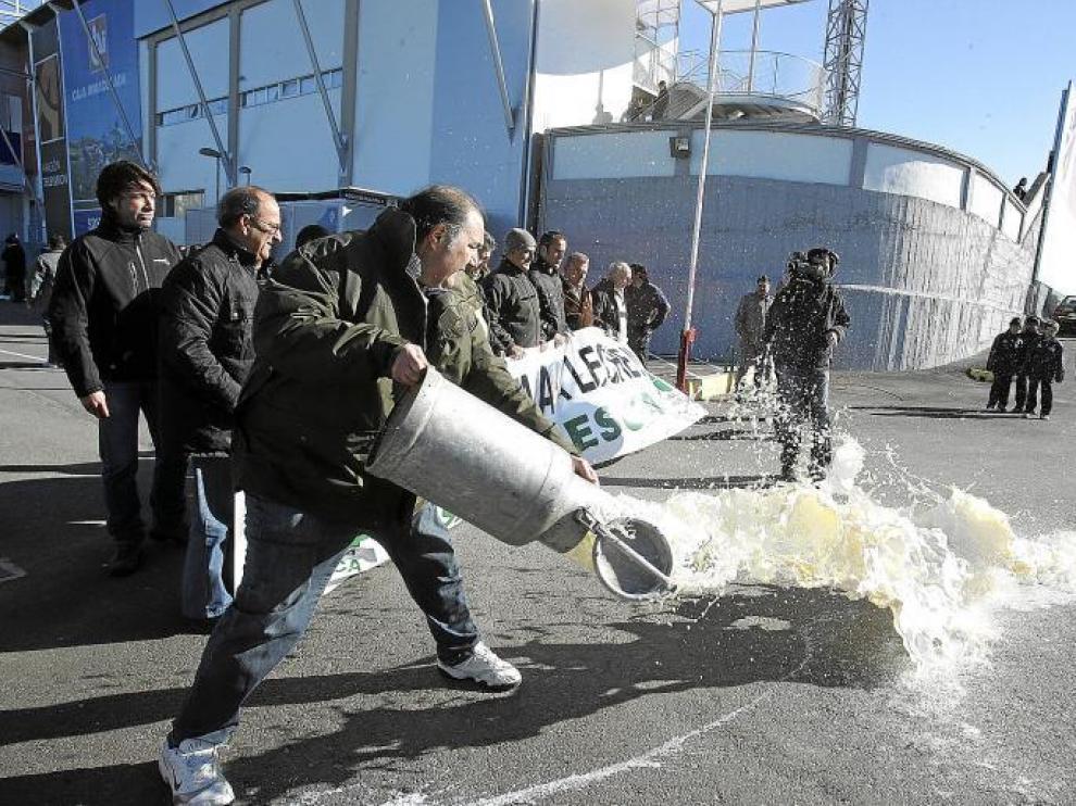 Fernando Luna, presidente provincial de Asaja en Huesca, arroja el contenido de una lechera junto al estadio del Alcoraz.