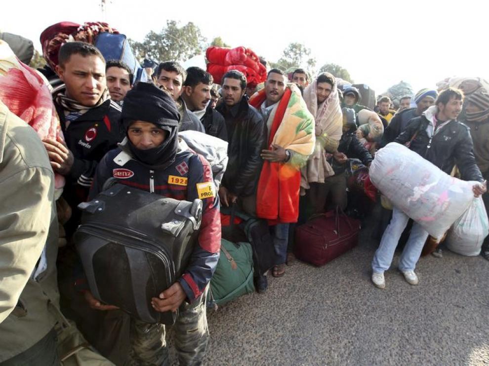 Ciudadanos egipcios residentes en Libia esperan junto a sus pertenencias en el paso tunecino de Ras el Jedir