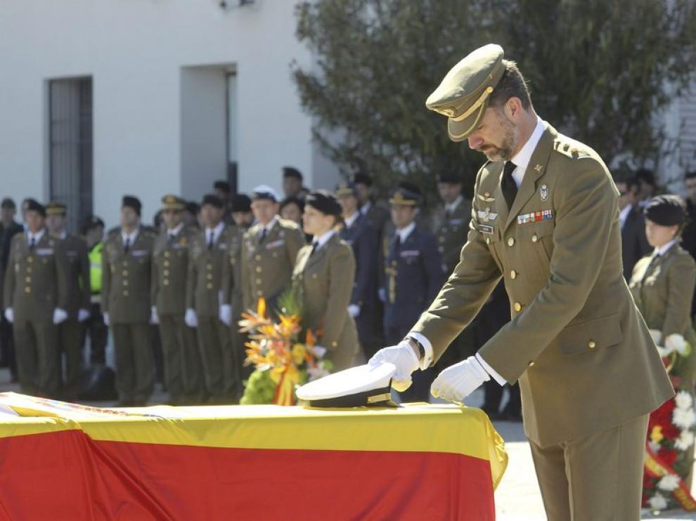 El príncipe de Asturias coloca la Cruz del Mérito Militar con distintivo amarillo en uno de los féretros de los cinco militares muertos el pasado jueves