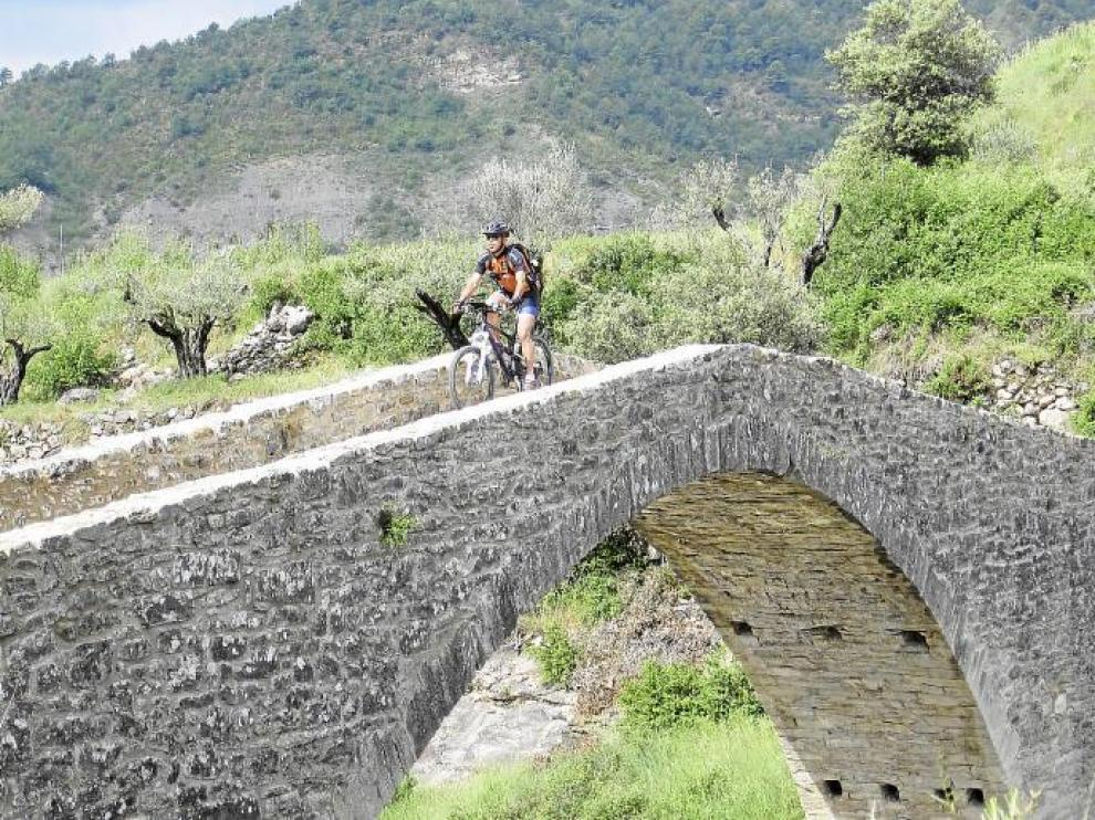 Un ciclista de BTT transita por un puente rehabilitado de la comarca de la Ribagorza donde Aramón Bike, también está presente.