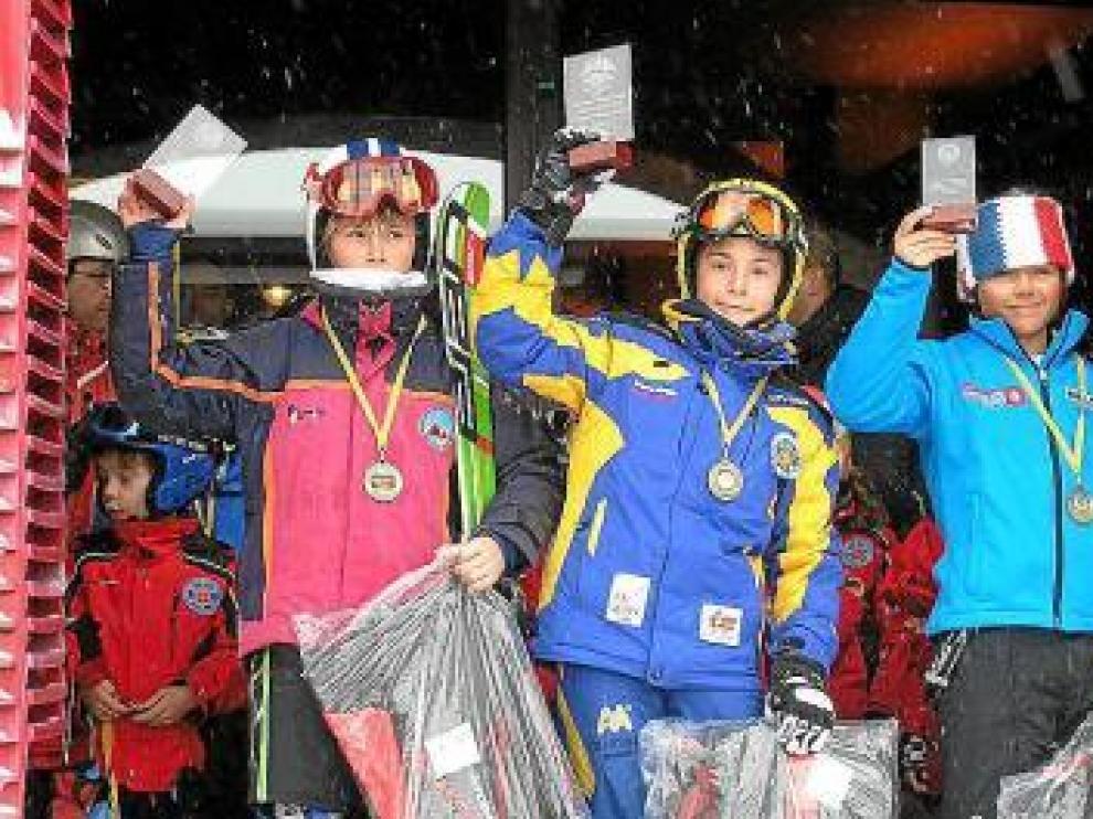 Los ganadores en Astún enseñan sus trofeos.