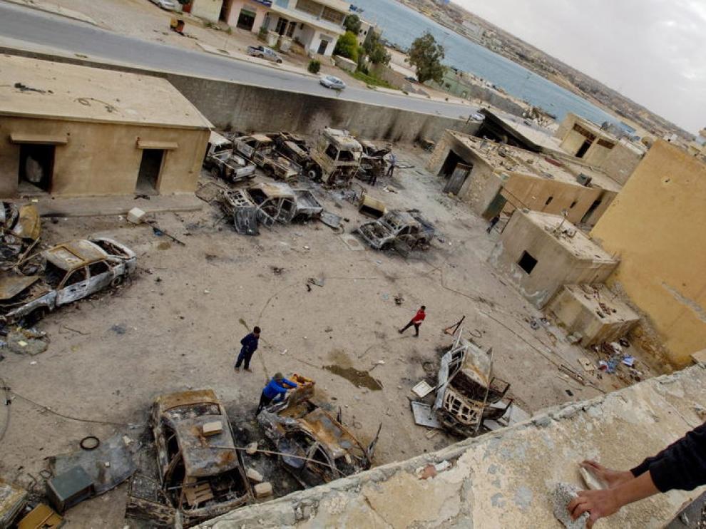 Un niño observa los vehículos quemados en el patio de una estación de policía en Tobruk (Libia)