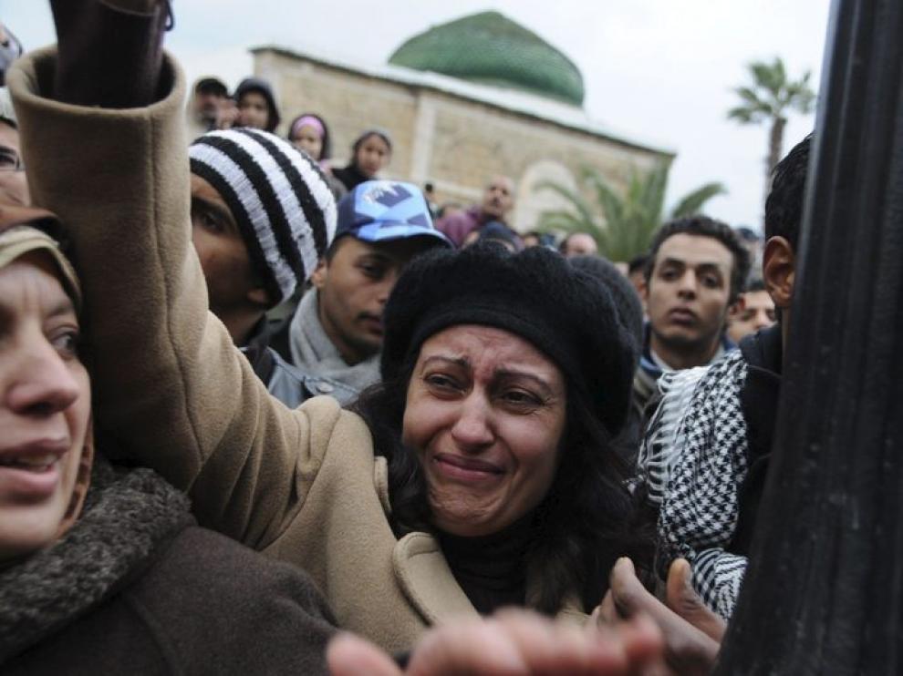 Una manifestante tunecina que llora, mientras cargan el ataúd del manifestante muerto