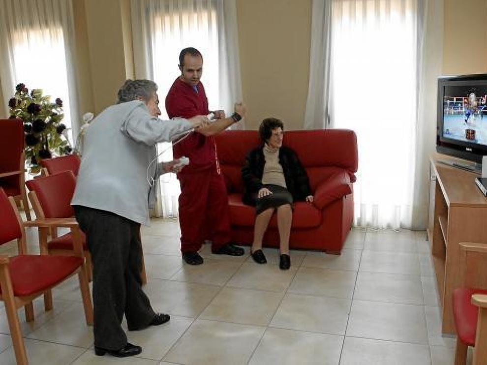 Bárbara Soler juega a la Wii mientras su terapeuta, Jesús Belmonte, le da indicaciones.
