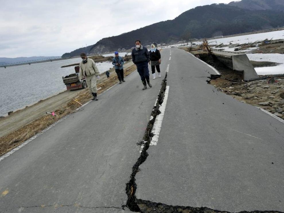 Un grupo de personas caminan por una carretera afectada por el terremoto y posterior tsunami
