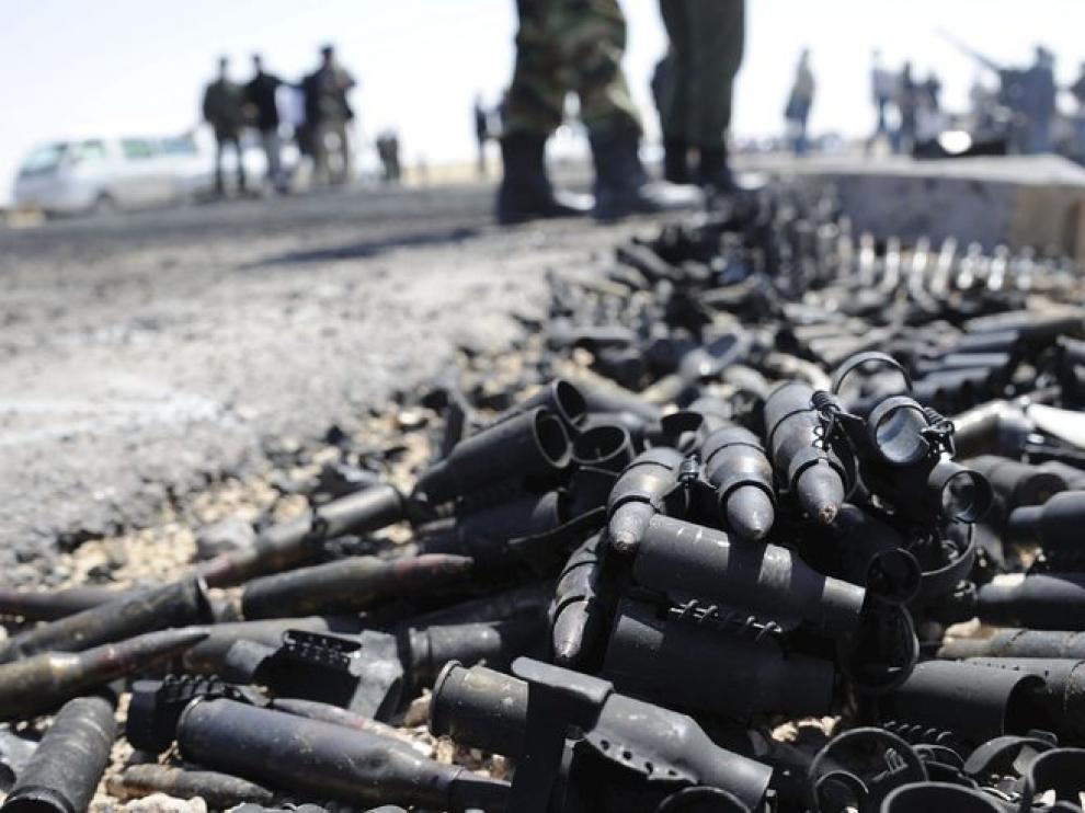 Rebeldes libios junto a munición destruida en una carretera que conduce a Briga