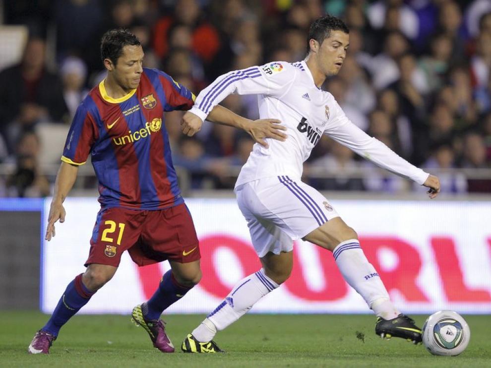 Cristiano Ronaldo controla un balón frente al defensa brasileño Adriano.