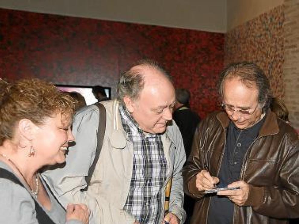 Serrat firma un disco para dos admiradores en La Almunia.