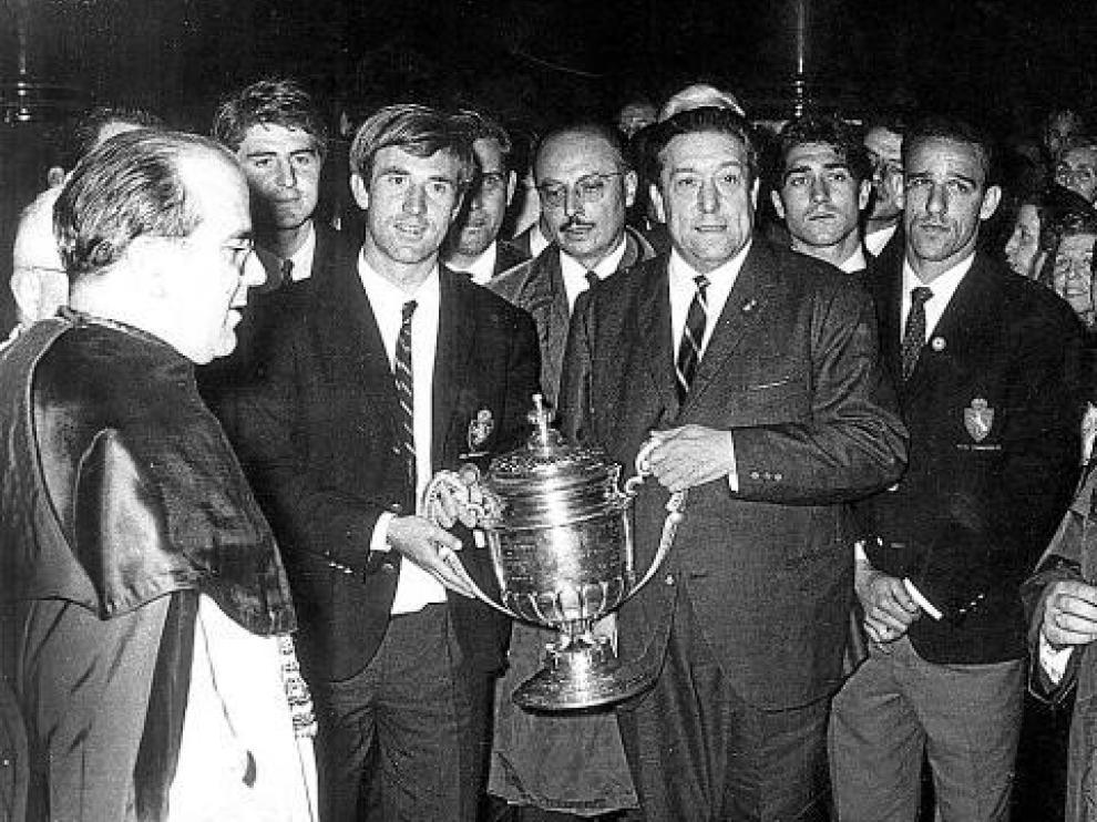 Lapetra sujeta el trofeo de Copa conseguido por el Real Zaragoza en 1966. Lo hace a la vez con Waldo Marco, presidente en aquella época. A la derecha figura el brasileño Canario.