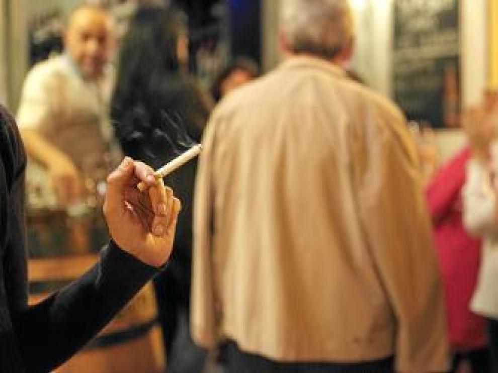 Imagen de una fumadora en la puerta de un bar.