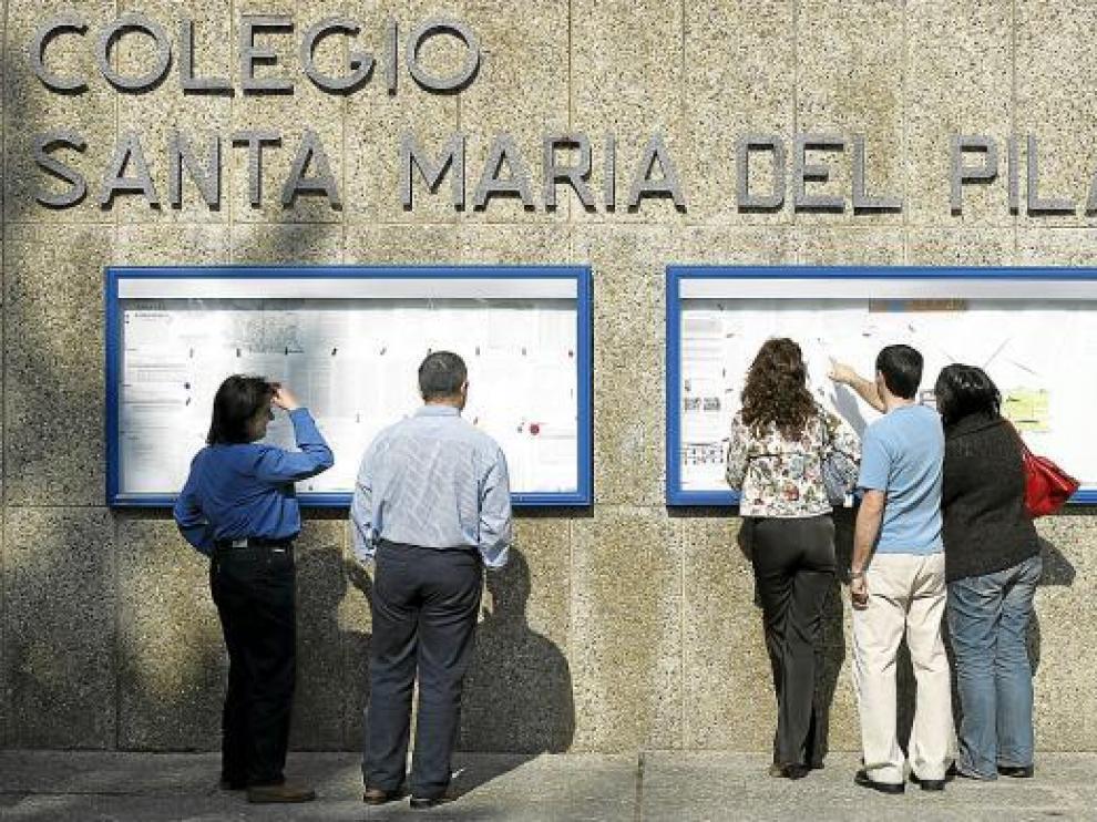 Unos padres leen los anuncios del tablón situado en la entrada de Marianistas.