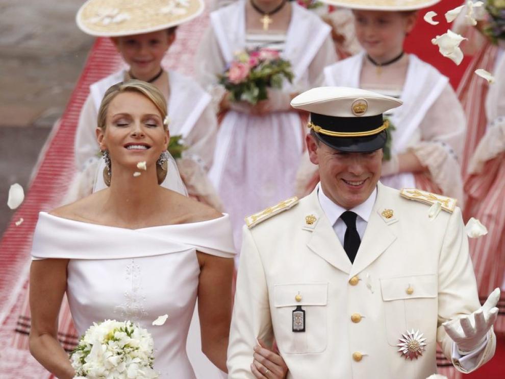 El príncipe Alberto II de Mónaco (d) y la princesa Charlene saludan a los invitados mientras abandonan el Palacio Real
