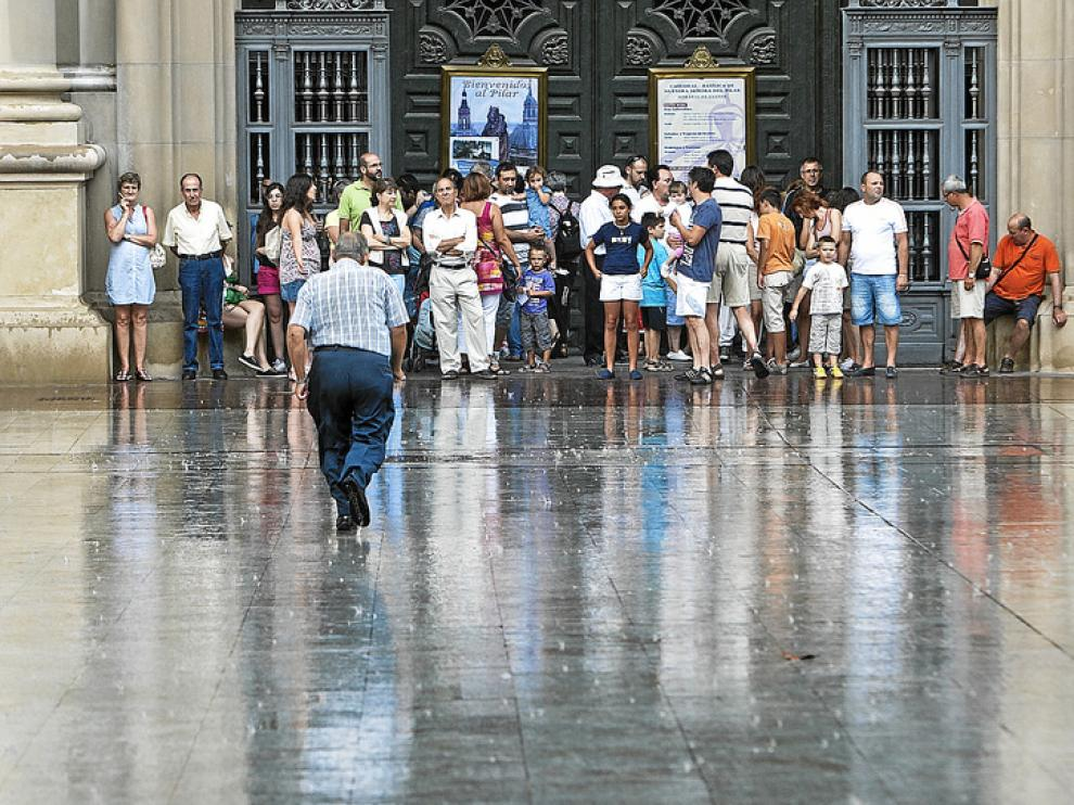 Paseantes y turistas se refugian de una tormenta en la entrada a la basílica del Pilar.