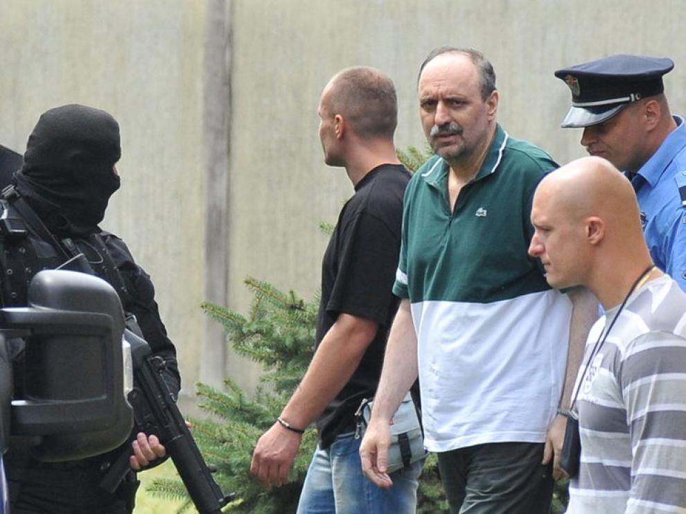El ex militar serbio Goran Hadzic es escoltado por la policía durante su traslado a La Haya.