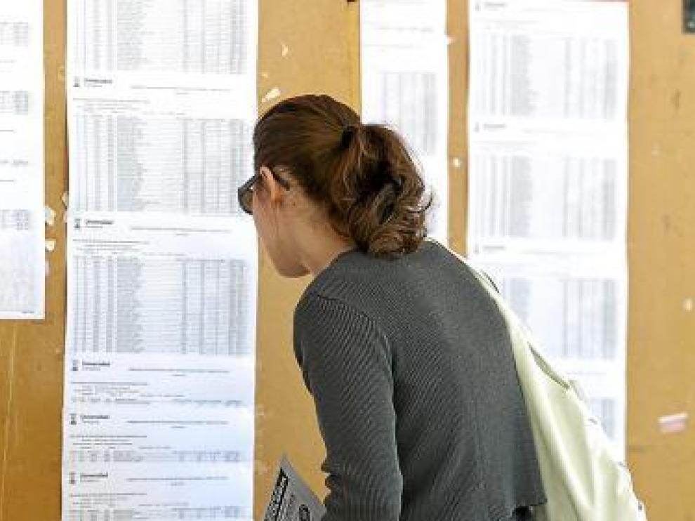 Una joven mira las listas de admitidos en la Universidad.