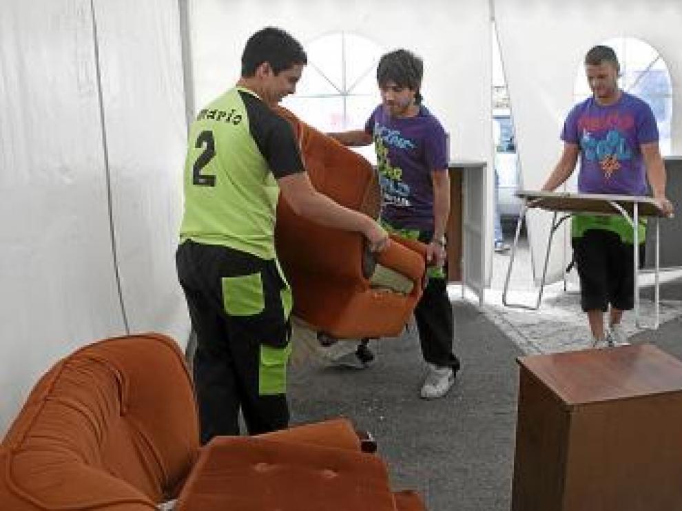 Mario, Héctor y Luis amueblan el espacio de una de las jaimas.
