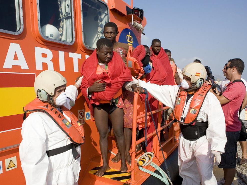 Efectivos de Salvamento Marítimo ayudan a bajar a algunos inmigrantes.