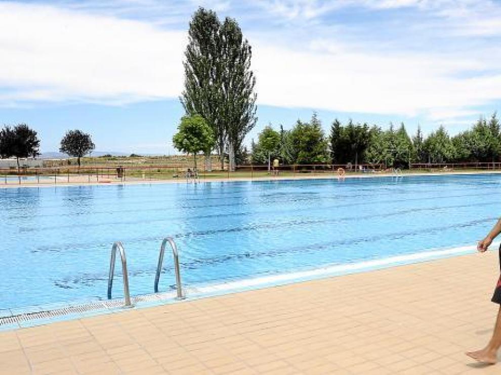 El socorrista, con una sudadera puesta, pasea por el borde de la piscina vacía de Los Planos.