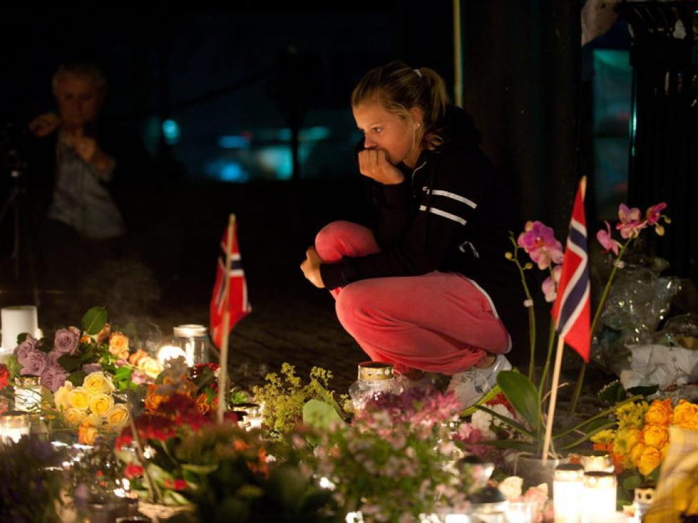 Una mujer permanece frente a las ofrendas dejadas en una iglesia de Oslo