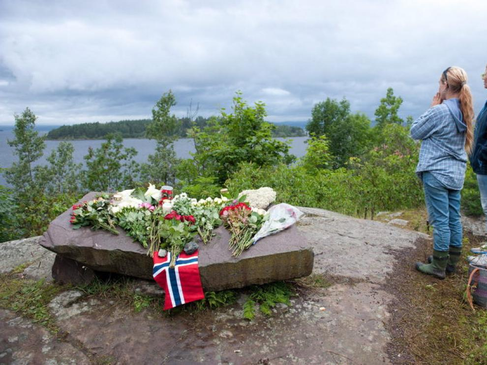 Algunas personas colocan flores frente a la isla de Utoya