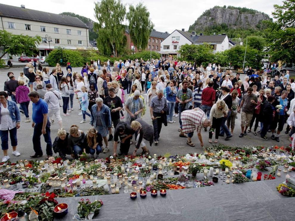 Ciudadanos noruegos dejando velas y flores en homenaje a las víctimas