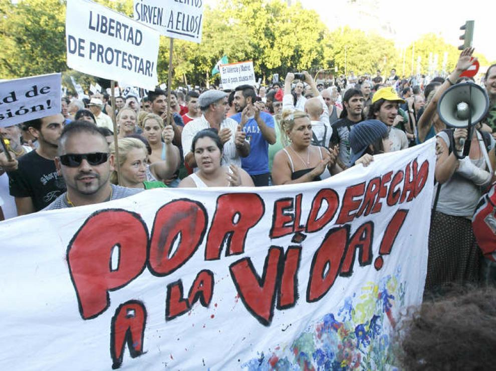 Varios indignados muestran su pancarta durante la concentración en la Plaza de Atocha