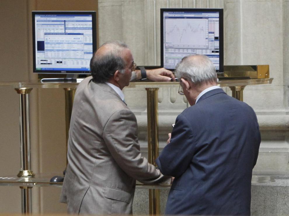 Dos inversores consultan los datos económicos en la Bolsa de Madrid
