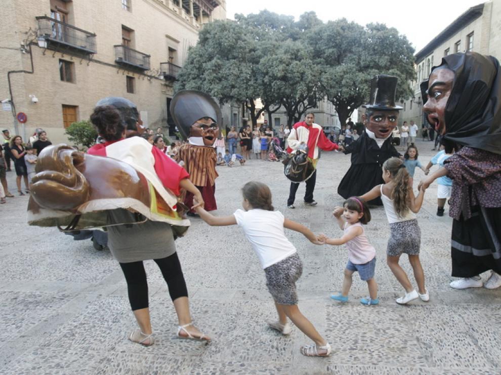 Los niños aprovecharon el ensayo de gigantes y cabezudos en la plaza de la Catedral para divertirse.