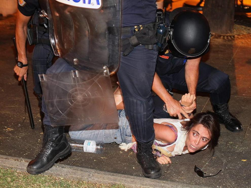 Un policía reduce a una de los manifestantes en Madrid