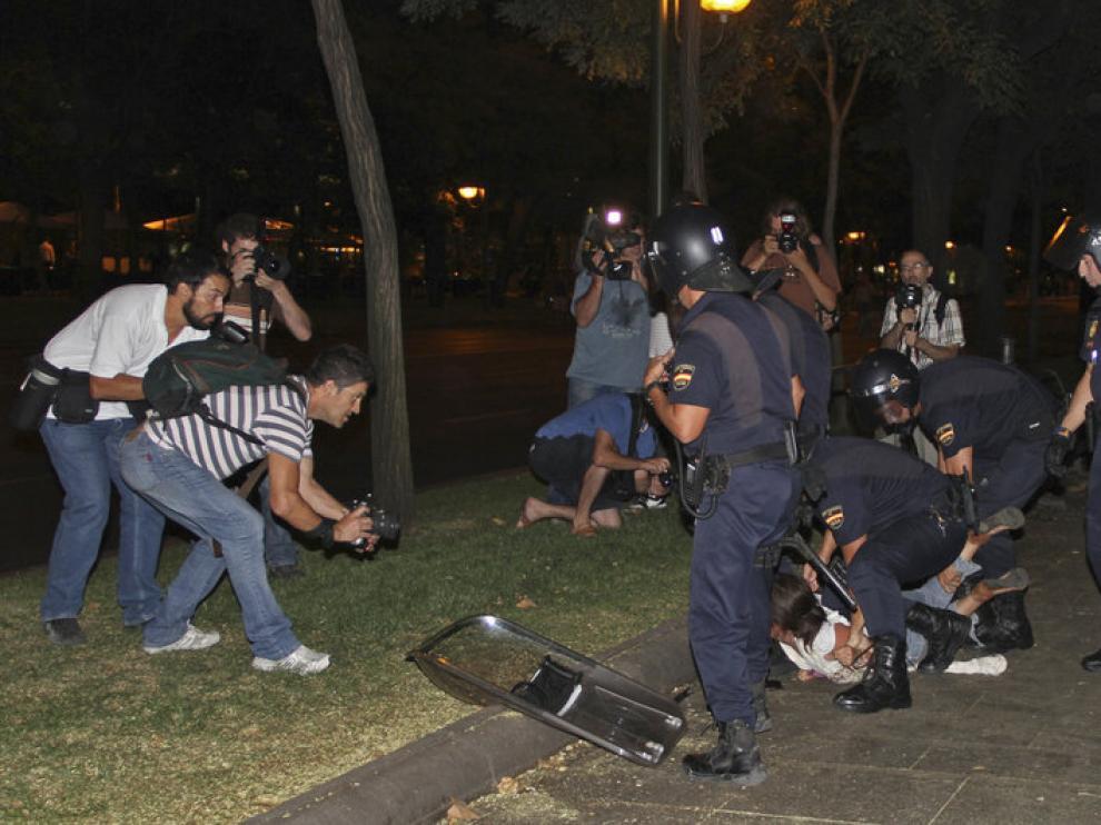 Miembros de la Policía Nacional retienen a un joven durante los disturbios de la noche del jueves