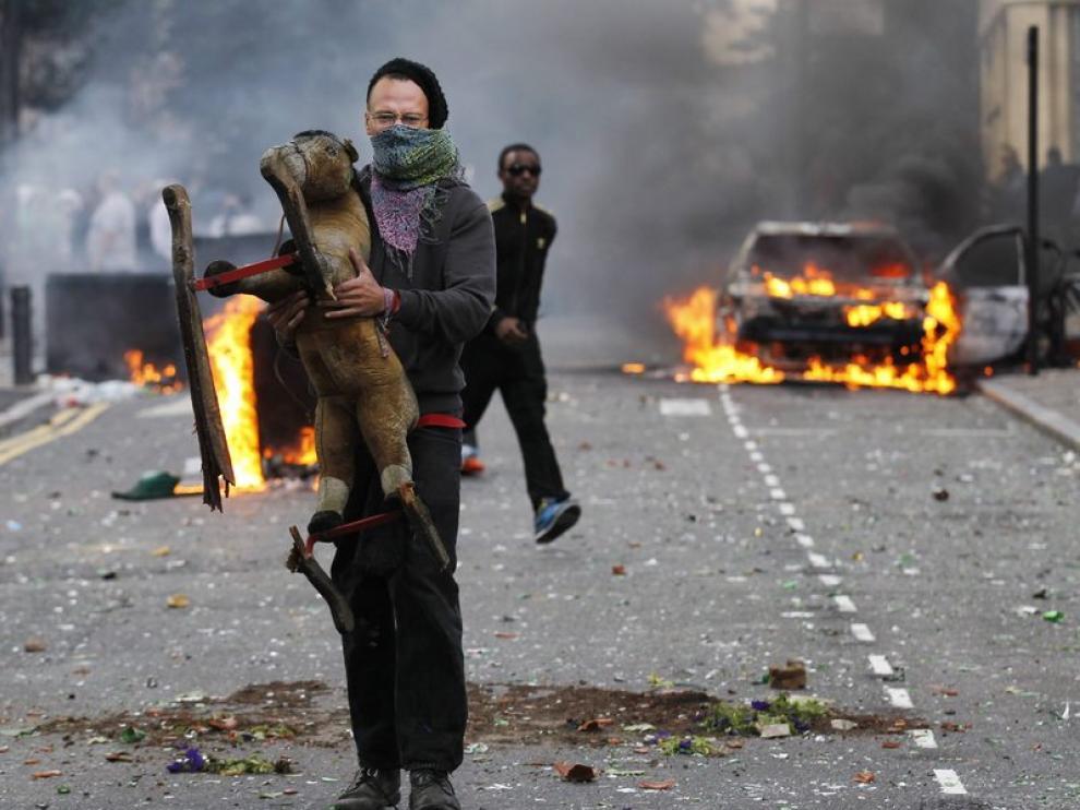 Un joven sujeta un juguete frente a un coche ardiendo
