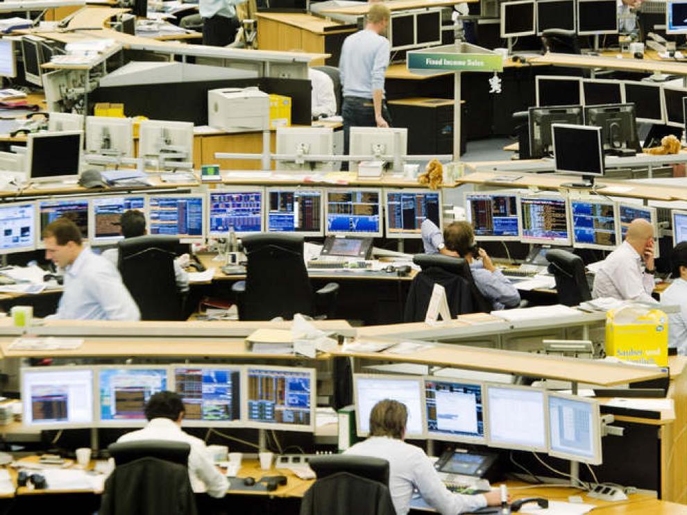 Corredores de bolsa holandeses observan la evolución de los distintos valores en sus pantallas