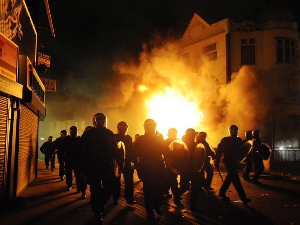 Policías antidisturbios han rodeado este martes un edificio incendiado en el barrio de Croydon