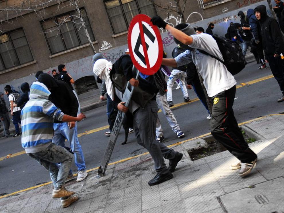 Manifestantes arrancan del suelo una señal en Santiago de Chile