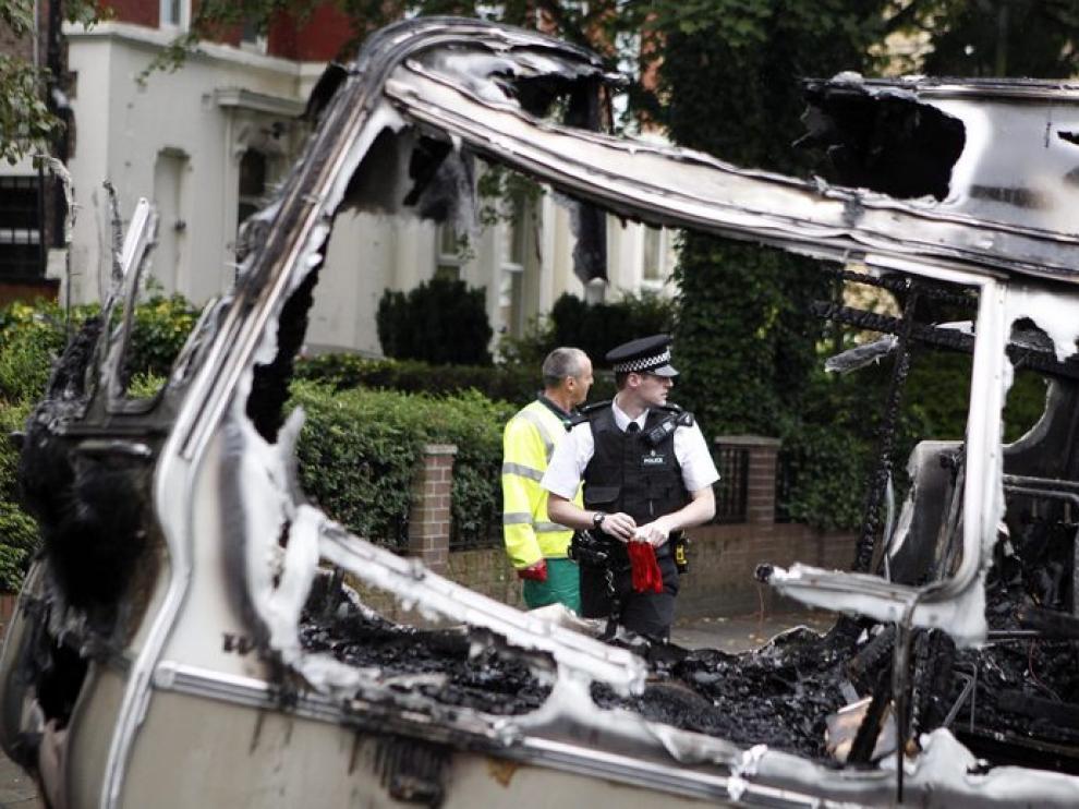 Un policía y un trabajador de la limpieza retiran los escombros de un vehículo en Liverpool