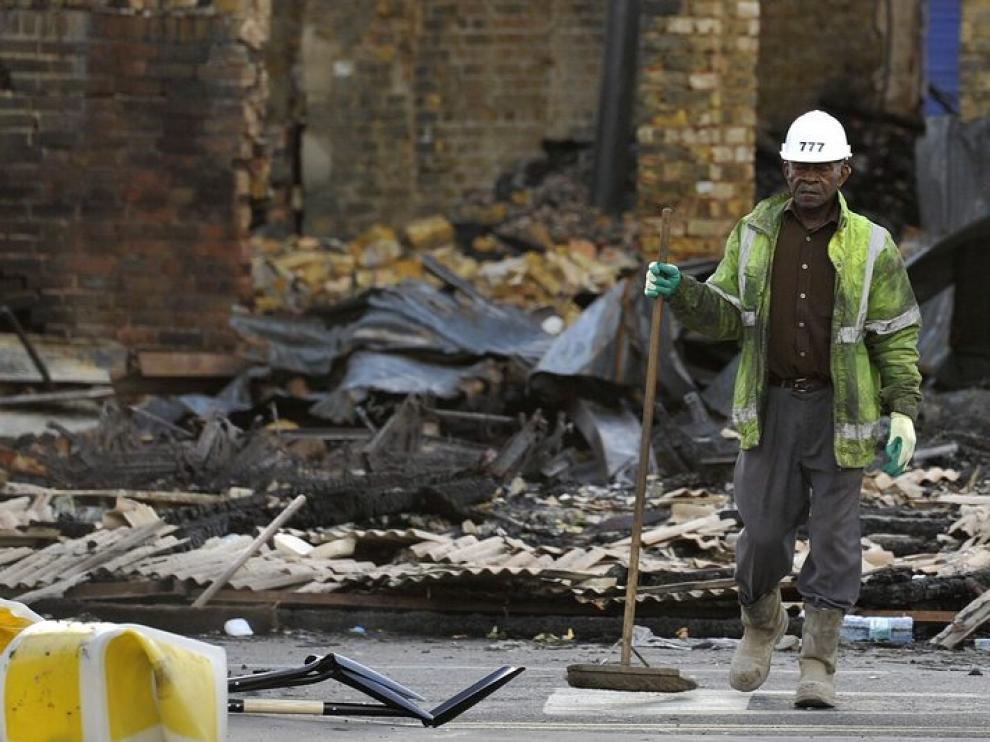 Un trabajador limpia los escombros de lo que era una tienda de muebles al sur de Londres