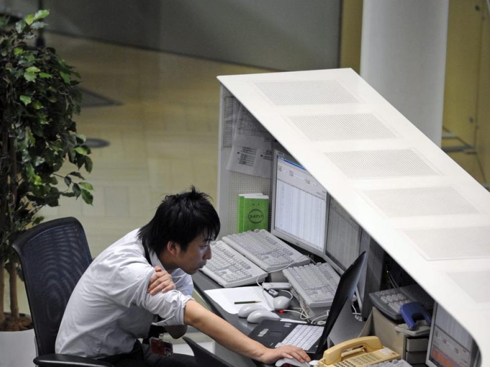 Un corredor de bolsa observa los datos bursátiles en un ordenador en la bolsa de Tokio