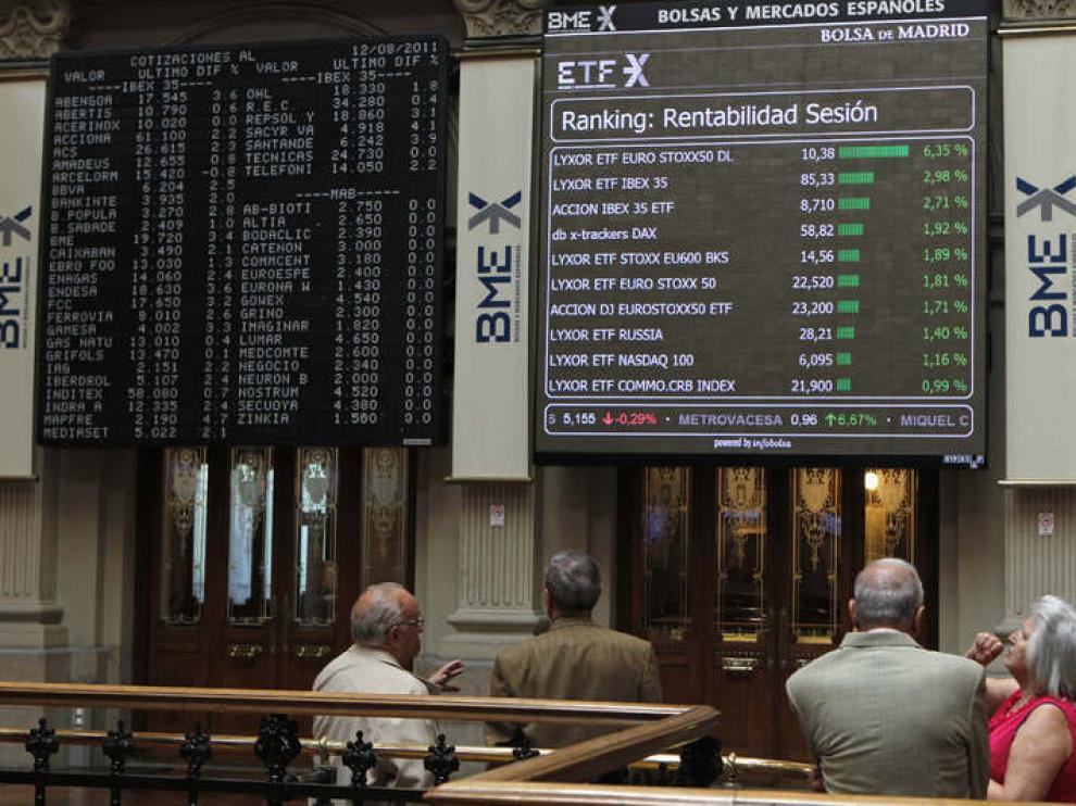 Varios operadores observan un panel en la Bolsa de Madrid