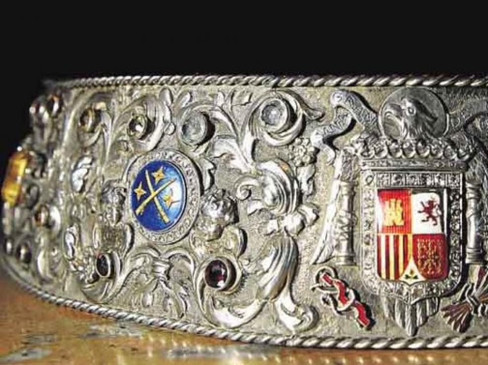 Broche que sujeta habitualmente el manto. Arriba, uno de sus esmaltes, con el escudo del Cabildo