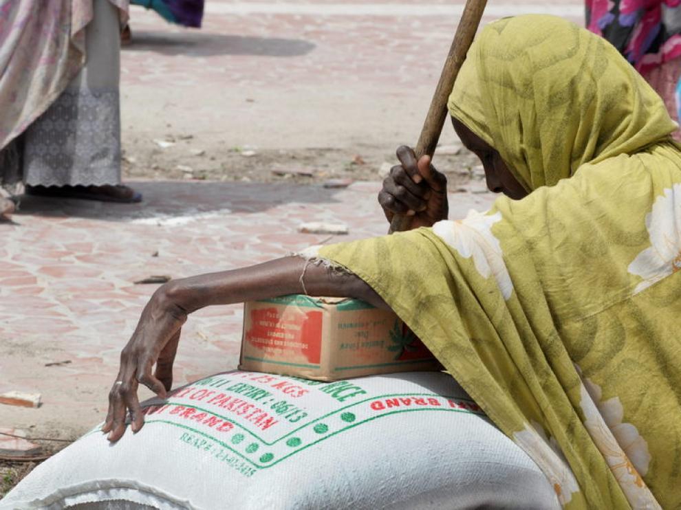Una anciana refugiada apollada encima de un saco de arroz