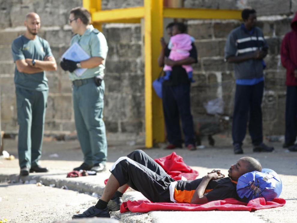 Un inmigrante descansa en el suelo tras ser trasladado al puerto de Tarifa