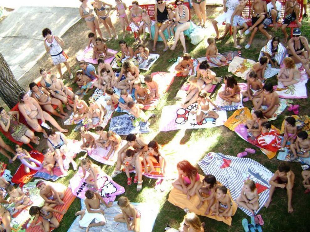 Los bañistas extienden sus toallas para escuchar los cuentos en la piscina de Fraga.