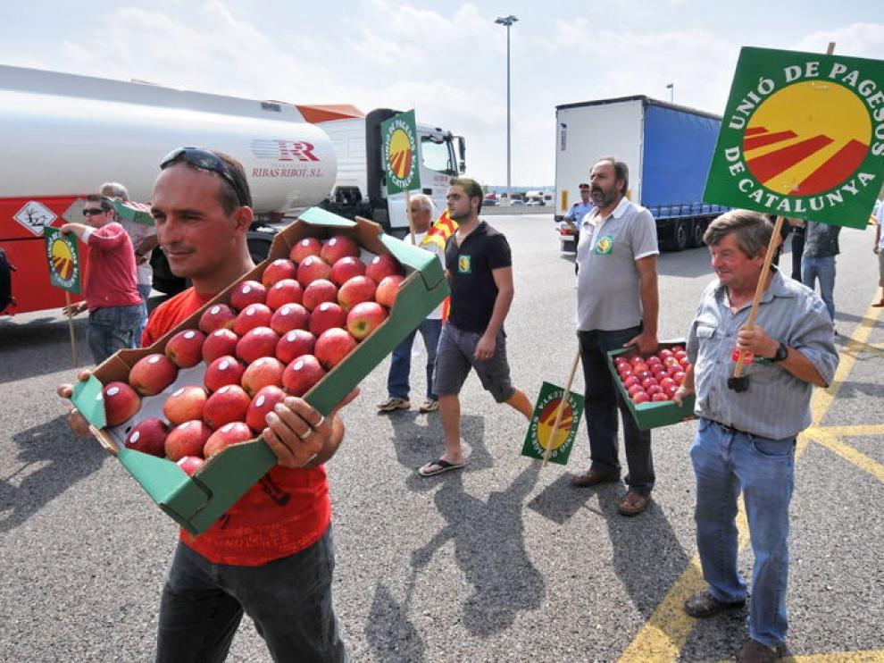 Un grupo de agricultores repartiendo fruta en la frontera de la Junquera